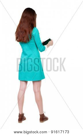 back view of standing young beautiful  girl with tablet computer in the hands of.  Isolated over white background. The girl in a blue dress with brown shoes twists in the hands of a tablet.