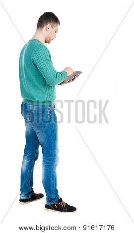 back view of standing young man with tablet computer in the hands of.  backside view of person.  Isolated over white background. The guy in the green jacket stands sideways and running on the tablet