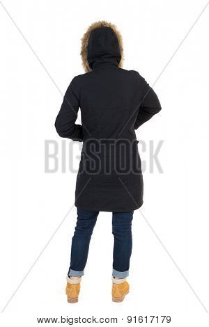 Back view woman in winter jacket  looking up.     Isolated over white background. Girl in a black winter jacket with a hood to hide his hands in his pockets