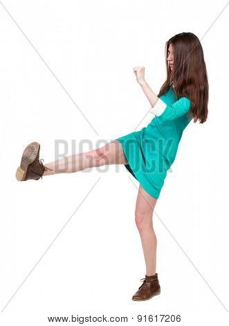 skinny woman funny fights waving his arms and legs. Isolated over white background. The girl in a green dress standing sideways strict and swings his left foot.