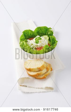 bowl of vegetable salad with cottage cheese and slices of bread on white place mat