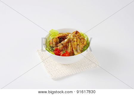 baked marinated chicken wings with fresh vegetable, served in the bowl