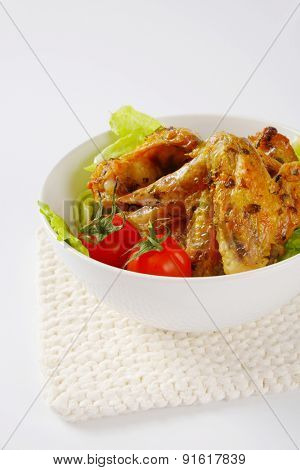 part view of bowl with baked chicken wings and salad