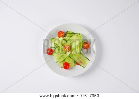 overhead view of plate with cucumber slices and halved cherry tomatoes