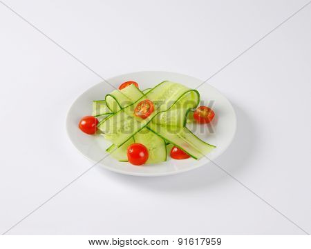 thin slices of cucumber with halved cherry tomatoes, served on the plate