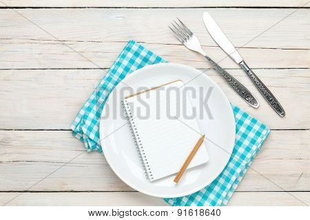 Notepad for recipe over empty plate and silverware on white wooden table background