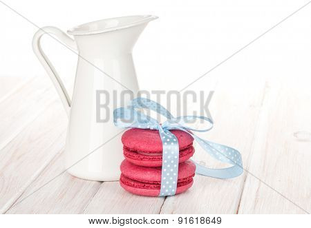 Red macarons with blue ribbon and milk jug on white wooden table