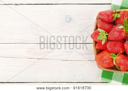 Fresh ripe strawberry in bowl over wooden table background. Top view with copy space