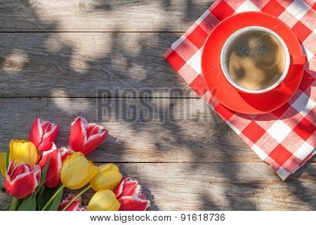 Colorful tulips and coffee cup on garden table. Top view with copy space