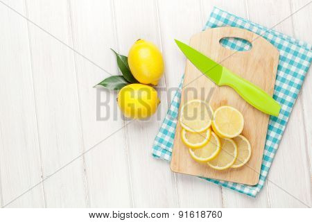 Sliced lemon on cutting board. Top view over wood table background with copy space