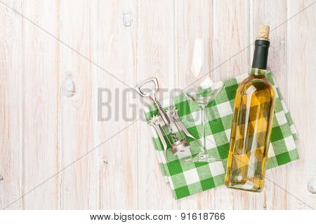 White wine bottle, glass and corkscrew on white wooden table background. Top view with copy space