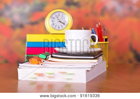 Books, cup with a saucer, alarm clock and writing-materials