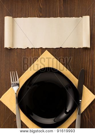 kitchen utensils at cloth napkin on wooden background