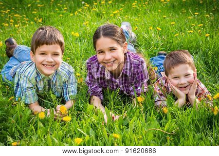 Three kids on green grass meadow