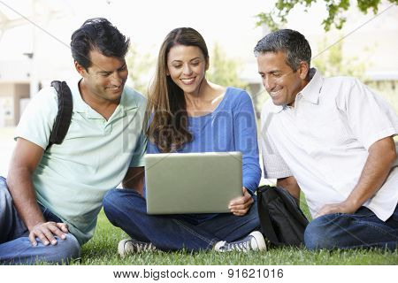 People using laptop outdoors