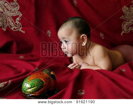 Baby boy lies on the Indian silver embroidered dark-cherry shawl