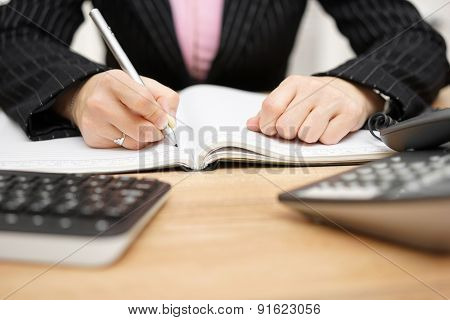Businesswoman Writing Notes At Her Desk