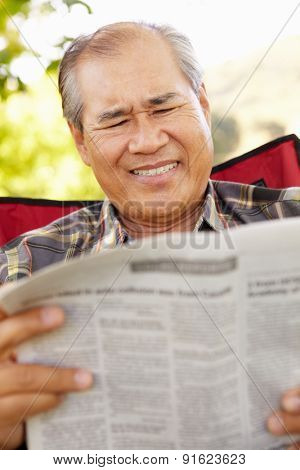 Senior Asian man reading outdoors