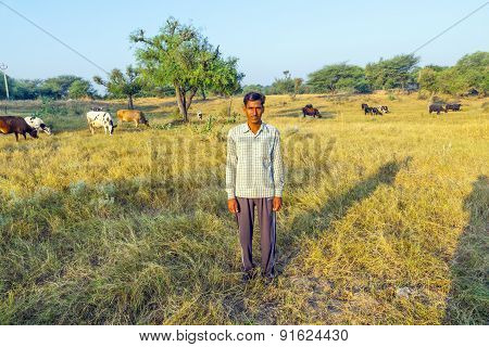 Farmer Poses In Front Of His Cows