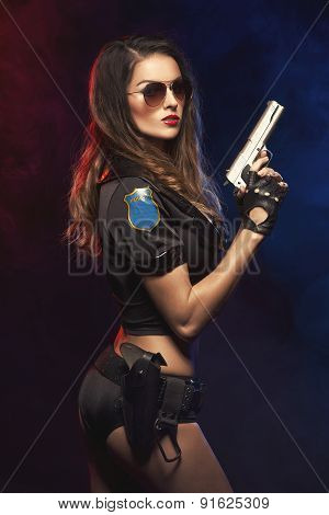 Sexy Woman With Police Uniform In Studio On Dark Red And Blue Background
