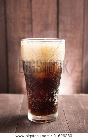Cola In Glass With Ice On Wooden Background
