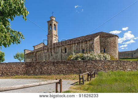 Old parish church under blue sky in town of Prunetto, Italy.