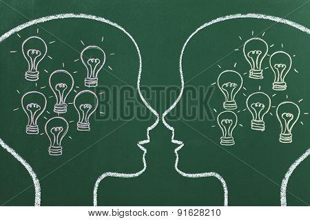two head shapes with lightbulbs inside drawed on blackboard