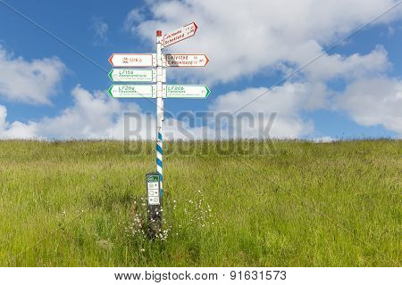 Bicycle Signpost In Grass With Blue Sky