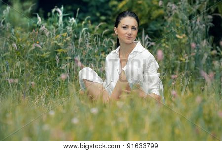 Young Relaxing Woman Sitting In The Grass, Outdoors, Daylight. Beautiful Girl In A White Dress Posin