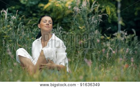 Young Relaxing Woman Sitting In The Grass With Closed Eyes, Outdoors, Daylight. Beautiful Girl Relax