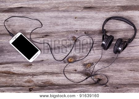 Smart phone with headphones against wooden background