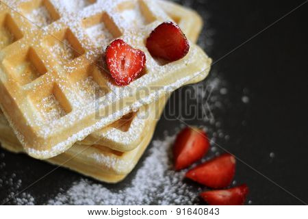 waffles with strawberries on dark background