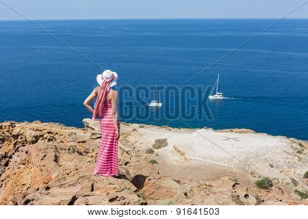 Woman In A Long Summer Dress Standing On A Cliff Sea.