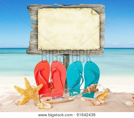 Summer beach with colored sandals and blank wooden poster. Blur azure sea on background