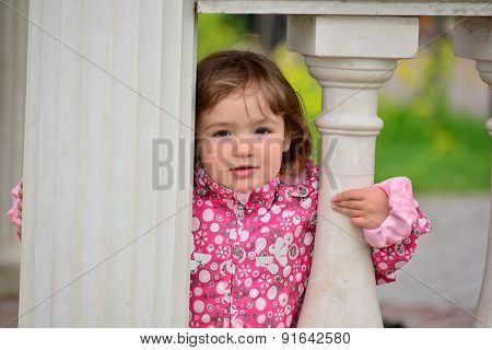 Two Year Old Girl Looks Out From  Gazebo