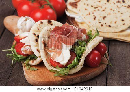 Piadina romagnola, italian flatbread sandwich with rocket salad, mozzarella cheese and prosciutto