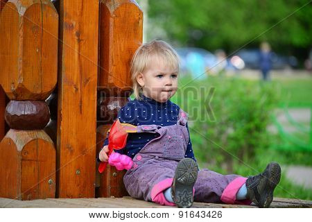 Two Year Old Girl On  Park Bench