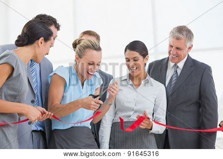 Happy business team cutting red ribbon in the office