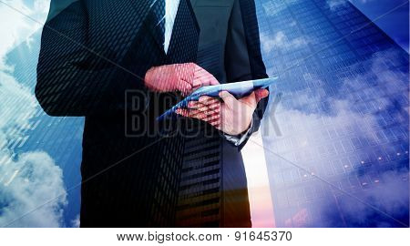 Businessman touching his tablet pc against low angle view of skyscrapers