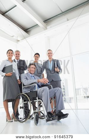 Disabled businessman with his colleagues smiling at camera in the office