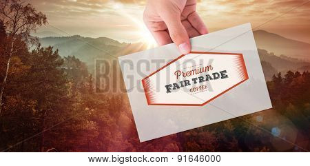 Hand showing card against sunrise over mountains