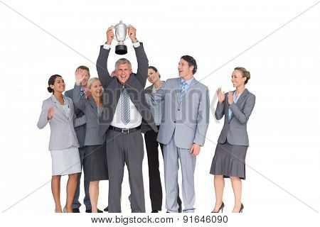 Excited business team cheering at camera with trophy on white background