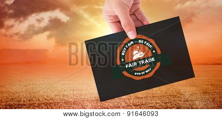 Hand showing card against sunrise over field