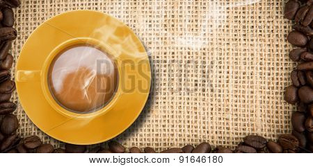 Yellow cup of coffee against frame of coffee beans