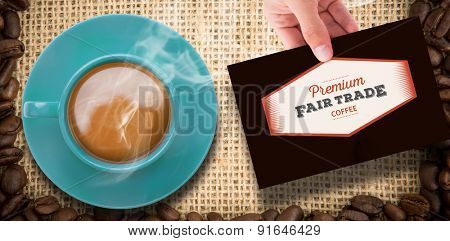 Hand showing card against frame of coffee beans