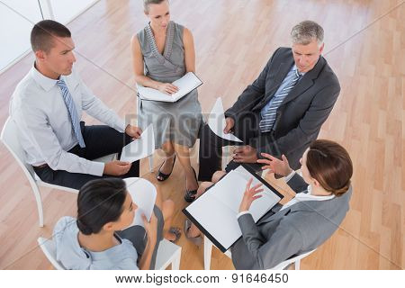 Business team sitting in circle and discussing in the office
