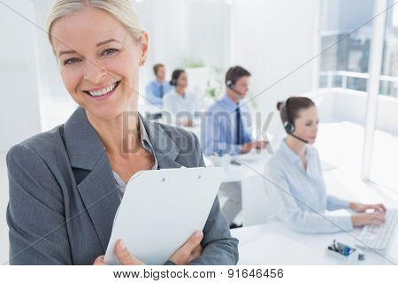 Smiling businesswoman holding a clipboard in call center