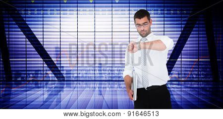 Serious businessman holding laptop checking time against business interface