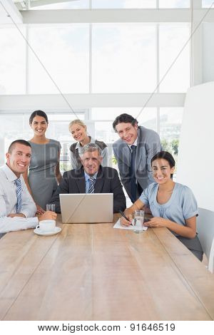 Smiling business team working together on laptop in the office
