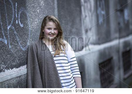 Teenage girl standing near the wall of the house.